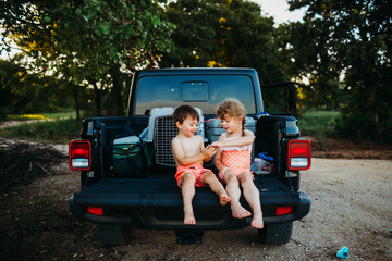 Young girl and boy sitting in bed of Jeep truck in swim suits