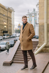 Pretty blond caucasian man in beige coat, with dark blue scarf tied around his neck, brown pants and dark leather shoes keeps hands in pockets. Selective focus on handsome hipster. Fashion concept.