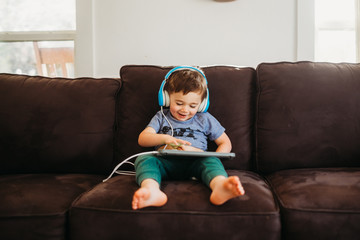 Young boy smiling playing with tablet on couch in livingroom