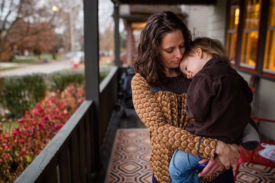 A small child rests head on his mother's shoulder on porch at twilight