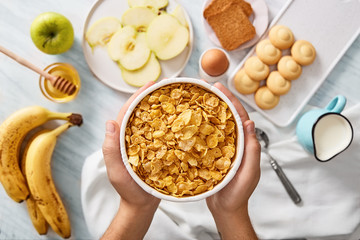 Man holding bowl of cereals. Rich breakfast ingredients. Top view