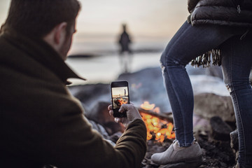 A man takes a picture of a campfire with his cell phone or smartphone