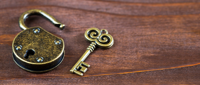 Escape room game concept, vintage golden key and opened padlock, web banner with copy space