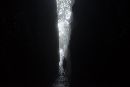 Silhouette of a tall unrecognisable woman looking out from a dramatic cleft in the rocks of the mountains of Madeira island. The light forms a V shape with a path passing through. Horizontal photo.