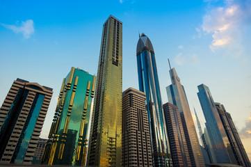 Recess Fitting Dubai Avenue of slender skyscrapers jutting into blue desert sky in Dubai