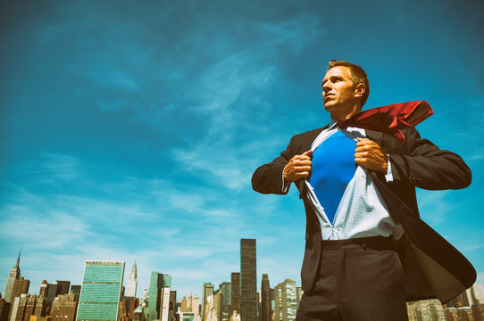 Confident young businessman revealing his inner superhero above the city skyline in bright sunny blue sky