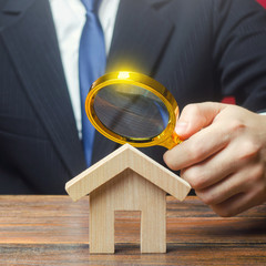 Photo sur Aluminium Pays d Europe A man is studying a house through a magnifying glass. Fair value of real estate. Property valuation. Legal deal. Standards and quality of construction. Legality and transparency of purchase agreement.