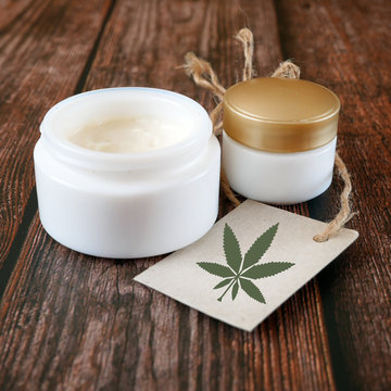 cannabis cosmetic, hemp cream in dose with cannabis leaf symbol in blank on wooden background, cosmetic with CBD oil