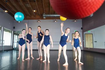 Group of young girls in dance class studio throwing balls in game of dodge ball