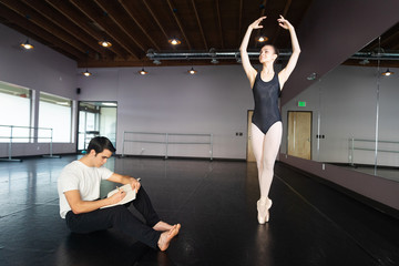 Artist draws in his sketch book as a ballerina model poses in a dance studio