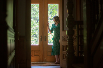 Thoughtful Woman standing by closed doors at home