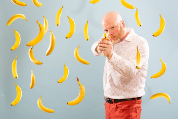 Bald man surrounded by bananas pointing fake banana gun