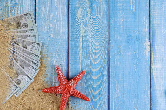 Red starfish on sand beach and US Dollar bill on blue wooden background