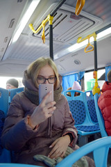 blonde teenager on the bus taking a picture with mobile