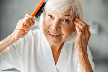 Cheerful old woman brushing hair and touching her temple