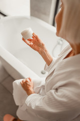 Elderly woman in bathrobe holding jar of cream