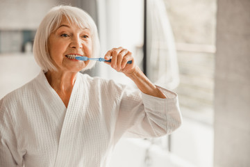Elderly woman in bathrobe brushing teeth in the morning