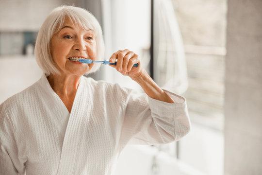 Elderly woman in bathrobe brushing teeth in the morning
