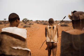 original native bushman from Namibia with traditional clothing from behind