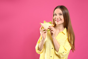 Young woman with tasty sandwich on pink background