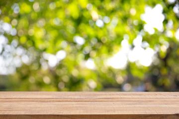 Empty wooden table with Defocus nature green bokeh, abstract nature background.
