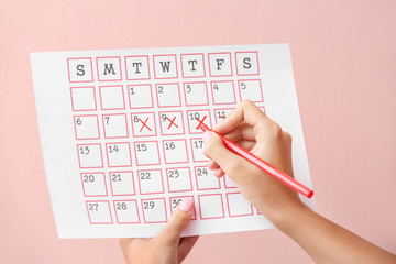 Woman with menstrual calendar on color background