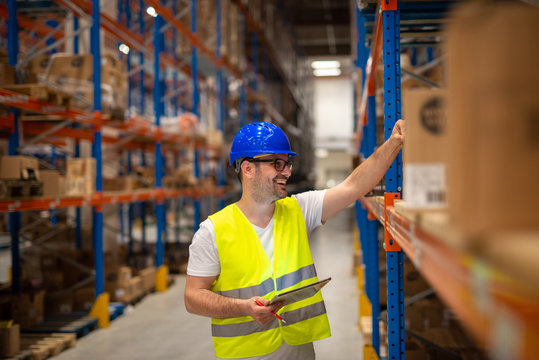 Warehouse worker looking at shelves with packages and checking inventory of large warehouse storage distribution area.