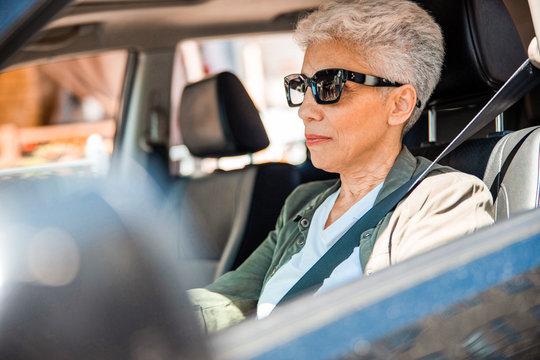 Elderly lady in sunglasses sitting in auto