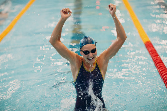 Young woman swimmer portrait joy rejoices in victory in swimming competitions in swimming pool. Win concept.