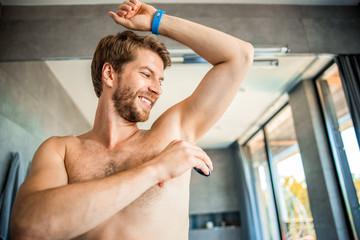 Joyful young man protecting skin from perspiring