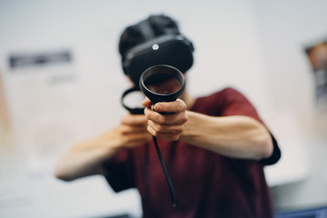 Young man in virtual reality goggles, vr glasses headset pointing with joystick in shooter