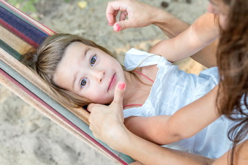 Little beautiful girl sitting in a hammock and smiling on a summer sunny day.
