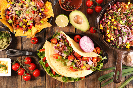 assorted of mexican food with fajitas, chili con carne and nachos with avocado, beef and cheese