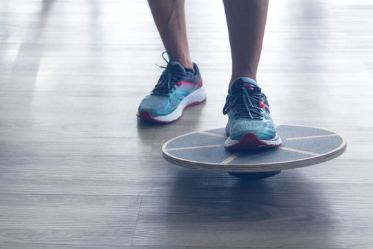 Mans legs in trainers testes balance board with one leg.