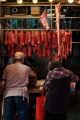 Butcher selling meat to older woman on street market store in Hong Kong