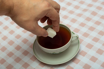 add a cube of white sugar to a cup of tea
