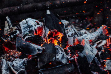 Smoldering coals on the grill with sparks. Bonfire Texture