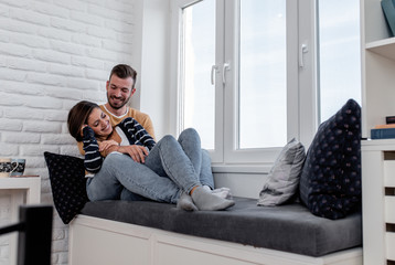 Photo sur Aluminium Kiev Young couple in love enjoying time together at home sitting by the window and relaxing in apartment.