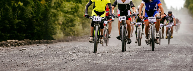 group cyclists athletes riding on gravel road on mountain bike