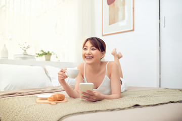 Young beautiful Asian smiling woman lying on bed and using smartphone.