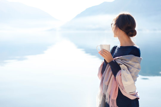Woman drinks morning coffee at sea beach. Cozy winter picnic. Girl enjoying calm nature, travel, relaxation, wellbeing. Blue background of mountains, still water. Copy space. Rear view female portrait