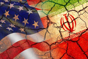 Concept of Conflict between USA and Iran war - US America and Iran flags on split up dried cracked...