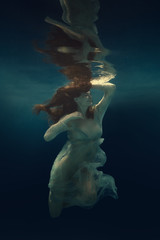 Portrait of a girl in a dress floating underwater