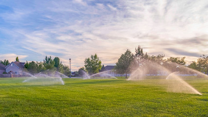 Pano frame Sprinklers watering green grassy field with homes and cloudy blue sky background
