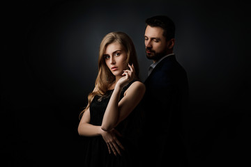 Fototapeta elegant couple on black background. handsome man and beautiful woman in black dress