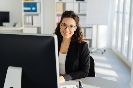 Young businesswoman sitting working at a desktop