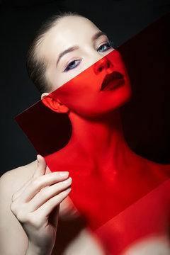 Bright contrasting beauty makeup portrait of a woman in blue and red shadow tones. Perfect clean skin and face makeup, dark lipstick on plump lips