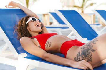 Fototapete - Photo of happy joyful woman smiling while lying on lawn chair