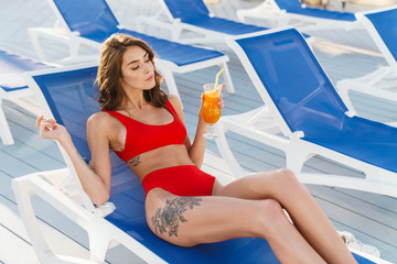 Fototapete - Photo of young calm woman drinking juice while lying on lawn chair