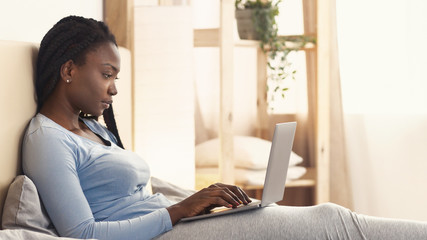 Wall Mural - African American Girl Using Laptop Working Sitting In Bed, Panorama